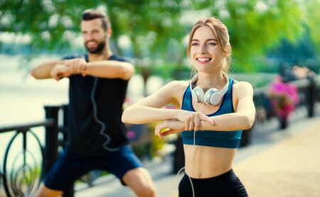 Young happy smiling lovely couple, or woman training with male bearded instructor, doing fit exercises together, outdoor. Fitness, sport workout, crossfit and healthy lifestyle concept. Stok Fotoğraf