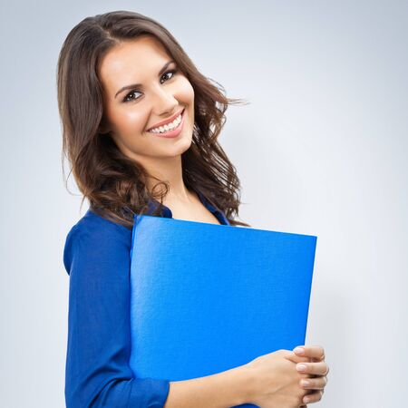 Portrait of young happy smiling businesswoman in corporate style with blue folder, with blank copy space area for slogan or text