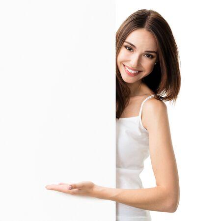 Uśmiechnięta urocza brunetka w białym podkoszulku dorywczo eleganckim ubraniu, pokazująca pusty pusty szyld z obszarem copyspace na tekst lub hasło, na białym tle
