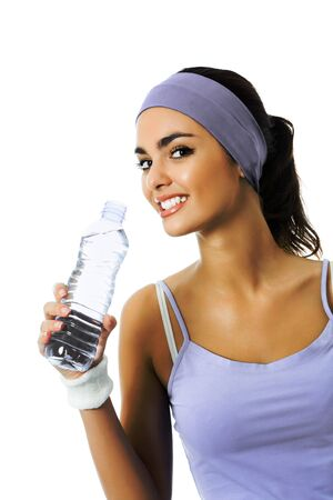 Happy smiling african american woman in sportswear drinking water, isolated against white background. Young female fitness instructor or personal trainer at studio shot.