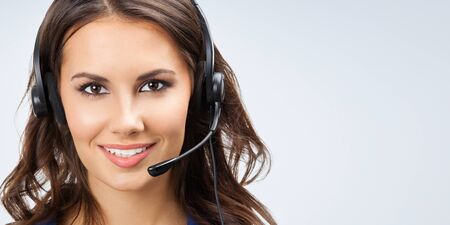 Portrait of happy smiling young support phone operator, sales phone agent or businesswomen in headset, with blank copyspace area for slogan or text