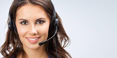 Portret szczęśliwego uśmiechniętego młodego operatora telefonicznego, agenta sprzedaży telefonu lub kobiet biznesu w zestawie słuchawkowym, z pustym obszarem copyspace na hasło lub tekst