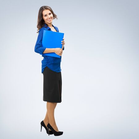 Full body portrait of young smiling businesswoman in corporate style with blue folder, with blank copy space area for slogan or text
