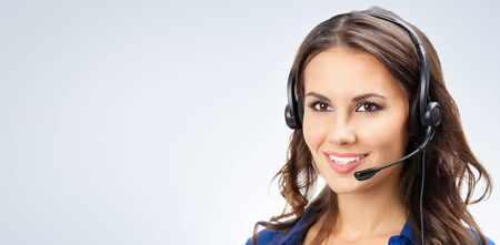 Portrait of happy smiling young support phone operator, sales phone agent or businesswomen in headset, with blank copy space area for slogan or text