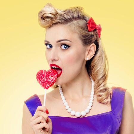 Reizende Frau, die Herzformlutscher, Pinupart, über gelbem Hintergrund isst. Kaukasisches blondes Mädchen im Retro-Mode und im Vintage-Konzept. Quadratische Komposition.