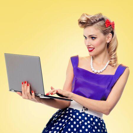 Schöne Frau mit Laptop, gekleidet in Pin-up-Stil Kleid, auf gelbem Hintergrund. Kaukasisches blondes Mädchen, das im Retro- Mode- und Weinlesekonzeptbild aufwirft. Quadratische Komposition. Standard-Bild