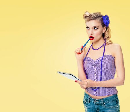 Lovely woman with notepad, in pin-up style clothing, on yellow background. Caucasian blond girl posing in retro fashion and vintage concept picture.