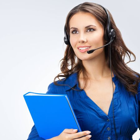 Portrait of happy smiling cheerful beautiful young support phone operator or sales phone agent in headset with blue folder, with blank copy space area for slogan or text 스톡 콘텐츠