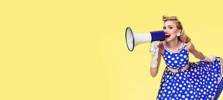Foto de concepto de ventas retro, vintage y de vacaciones - Mujer sosteniendo megáfono, vestida con vestido azul estilo pin up, sobre fondo amarillo. Modelo rubio caucásico - moda retro.