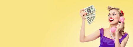 Happy lovely woman with money cash, talking on phone, dressed in pin up style dress in polka dot, over yellow color background. Caucasian blond girl in retro fashion and vintage concept.