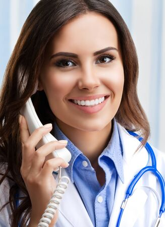 Portrait of happy smiling young doctor on phone, at office. Healthcare, medicine and medical staff concept.