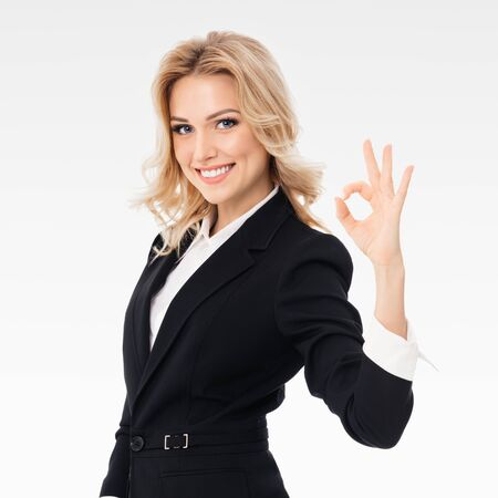 Happy smiling beautiful young businesswoman in black confident suit, showing okay gesture, on grey background, square composition picture