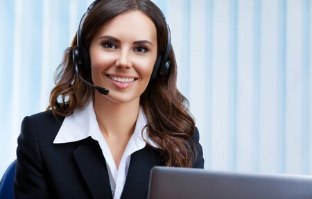 Portrait picture of customer support female phone operator or sales agent in headset and confident black suit, working with laptop at office workplace. Consulting and assistance service call center.