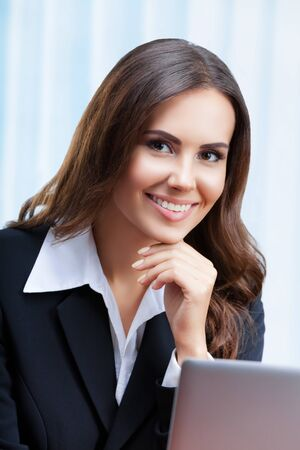 Portrait picture of happy smiling attractive businesswoman in black confident style suit working with laptop computer at office. Success in business, job and education concept shot.