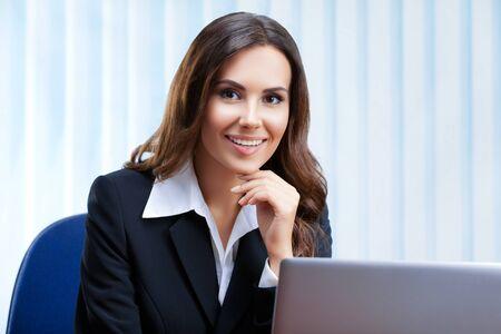 Portrait picture of attractive businesswoman in black confident style suit working with laptop computer at office. Success in business, job and education concept shot.