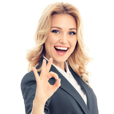 Happy smiling businesswoman in grey confident suit, showing okay hand sign gesture, over white background. Caucasian blond model in business success concept. Square composition.