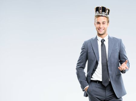 I am business king! Portrait of happy smiling young businessman in grey confident suit and crown, with copy space for some slogan or text. Leadership and business success concept.