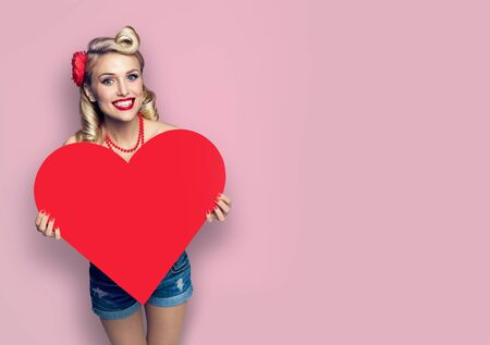 Woman holding red paper heart shape. Pin up girl. Retro fashion and vintage. Pink color background. Copy space for some slogan or sign text. Valentine or Like symbol. Banco de Imagens