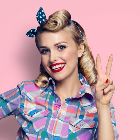 Pin up girl. Excited happy blond woman showing two fingers or victory gesture hand sign. Retro and vintage. Pink color background. Square composition.
