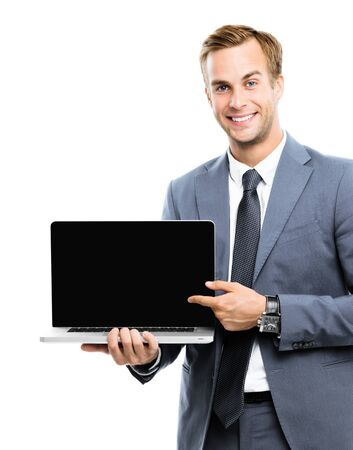 Smiling businessman in grey confident suit, showing blank laptop monitor, isolated over white background, with copy space area for some slogan, imaginary, ad or text.