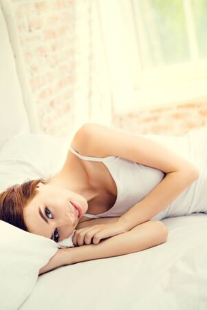 Beautiful happy smiling brunette girl waking up at home bedroom