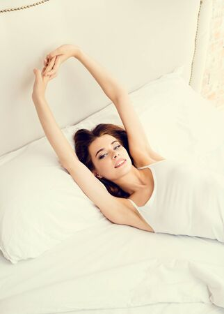 Portrait of beautiful happy smiling brunette girl waking up at bedroom