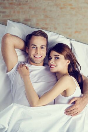 Portrait picture of young happy lovely couple on the bed at bedroom. Love, relationship, dating, happy people, bedtime concept.