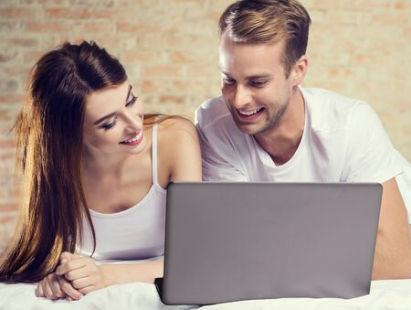 Beautiful young amorous couple using laptop, on bed. Internet, technology, family, love, relationship concept picture. Imagens