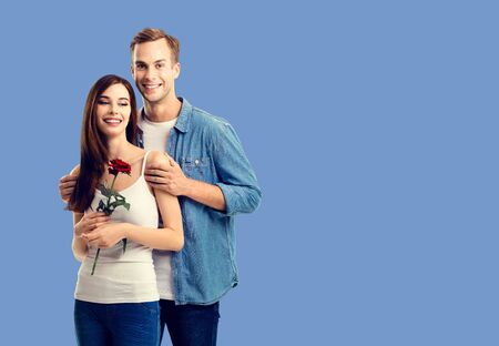 Love, relationship, dating, flirting, romantic concept - portrait of happy smiling hugging couple with flower, close to each other. Blue color background. Copy space.