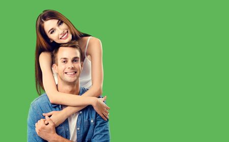 Love, relationship, dating, flirting, lovers, romantic concept - couple, standing close to each other and looking at camera, over green. Copy space for some text.