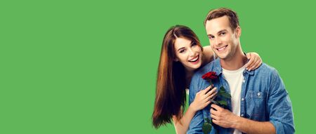 Love, relationship, dating, flirting, romantic concept - portrait picture of happy couple with flower, looking at camera. Green color background. Copy space for some text.