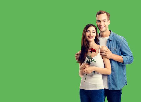 Love, relationship, dating, flirting, romantic concept - portrait of young happy smiling hugging couple with flower, close to each other. Green color background.