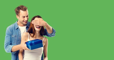 Love, dating, celebrating, lovers concept - happy amorous couple with blue gift box. Green color background. Copy space for some text.