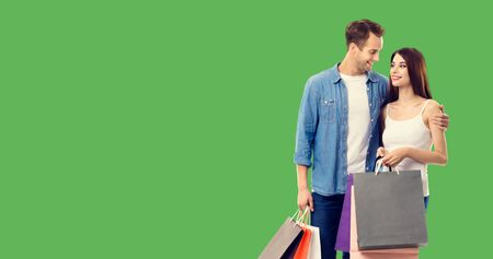 Love, holiday sales, shop, retail, consumer concept - happy couple with shopping bags, looking at each other. Green color background. Copy space for some text.
