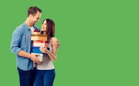 Love, relationship, dating, flirting, lovers, romantic concept - happy young couple holding gift boxes, close to each other. Green background. Copy space for some text.