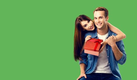 Love, relationship, dating, flirting, lovers concept - happy smiling amorous couple opening gift box. Green color background. Copy space for some text.