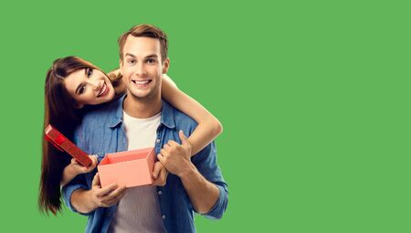 Love, relationship, dating, flirting, lovers, romantic concept - happy couple opening gift box, looking at camera. Green color background. Copy space for some text.