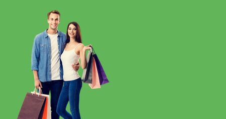 Love, holiday sales, shop, retail, consumer concept - happy couple with shopping bags, standing close to each other, and looking at camera. Green color background. 스톡 콘텐츠