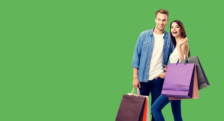 Love, holiday sales, shop, retail, consumer concept - happy couple with shopping bags, standing close to each other. Green background. Copyspace for some text.
