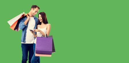 Love, holiday sales, shop, retail, consumer concept - happy smiling couple with shopping bags, and cellphone, standing close to each other. Green color background. 스톡 콘텐츠