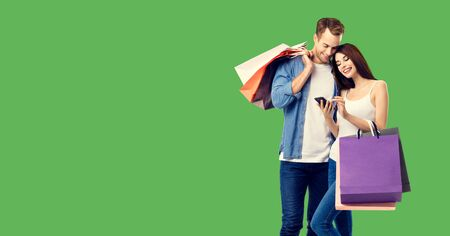 Love, holiday sales, shop, retail, consumer concept - happy couple with shopping bags, looking at mobile phone, standing close to each other. Green color background. 스톡 콘텐츠