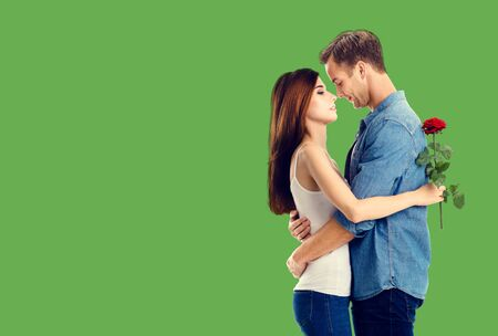 Love, relationship, dating, flirting, romantic concept - amorous hugging couple with flower, standing close to each other, against green background. Copy space.