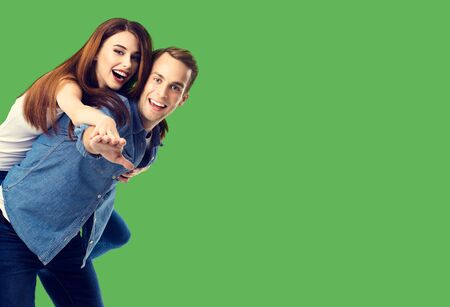 Love, relationship, dating, lovers, romantic concept - happy excited couple, in piggyback pose, over green background. Copy space for some text.