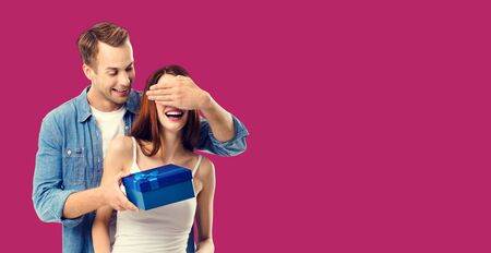 Love, dating, celebrating, lovers concept - happy amorous couple with blue gift box. Over red color background. Copy space for some text.