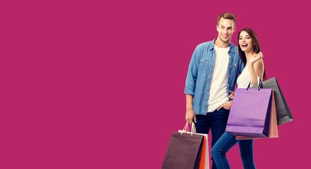 Love, holiday sales, shop, retail, consumer concept - happy couple with shopping bags, standing close to each other. Over red background. Copyspace for some text.