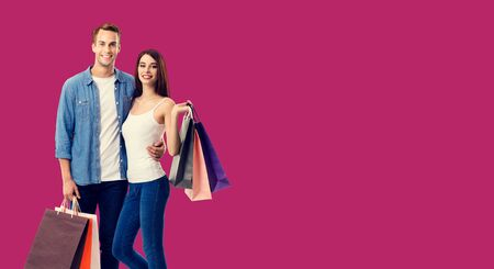Love, holiday sales, shop, retail, consumer concept - couple with shopping bags, standing close to each other. Over red background. Copy space for some text.
