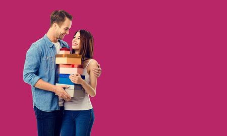 Love, relationship, dating, flirting, lovers, romantic concept - happy young couple holding gift boxes, close to each other. Red color background. Copy space for some text. 스톡 콘텐츠