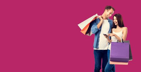 Love, holiday sales, shop, retail, consumer concept - happy smiling couple with shopping bags, and cellphone, standing close to each other. Over red color background. 스톡 콘텐츠