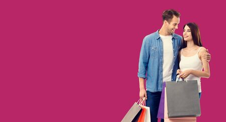 Love, holiday sales, shop, retail, consumer concept - happy couple with shopping bags, looking at each other. Over red color background. Copy space for some text.