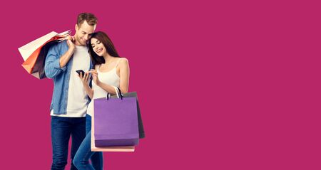 Love, holiday sales, shop, retail, consumer concept - happy couple with shopping bags, looking at mobile phone, standing close to each other. Over red color background. 스톡 콘텐츠